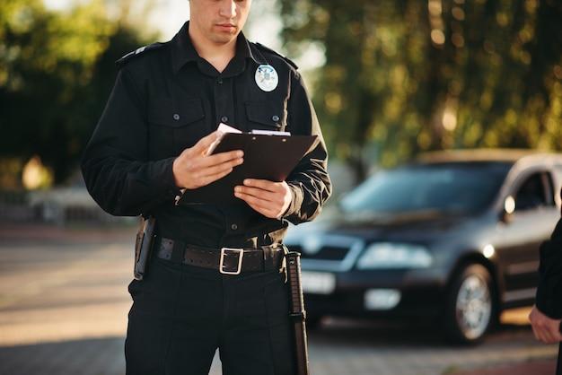 Policial com notebook nas mãos verifica o carro