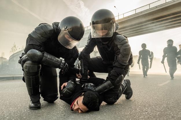 Policial de choque forte com capacetes torcendo os braços do manifestante nas costas enquanto o prendia na rua