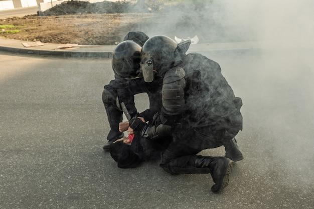 Policial de choque forte em trajes de camuflagem, colocando rebelde no chão enquanto usa força contra ele na rua