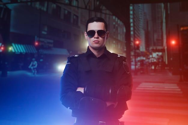 Policial de óculos escuros, cidade noturna