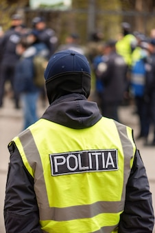 Policial e pessoas protestando por eleições antecipadas em frente ao prédio do tribunal constitucional