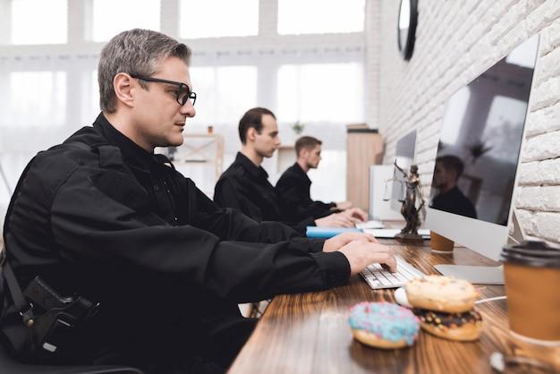 Policial está sentado no escritório e está digitando em um laptop.