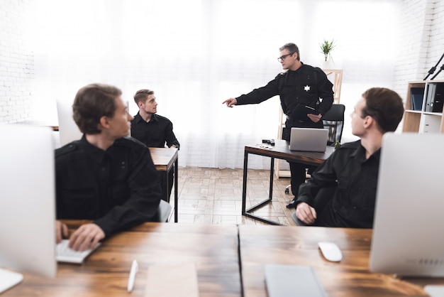 Policial instrui os subordinados na delegacia de polícia.