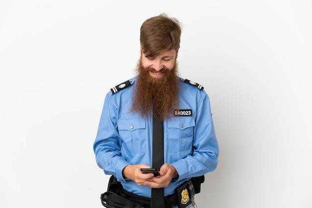 Policial ruivo isolado no fundo branco enviando mensagem com o celular