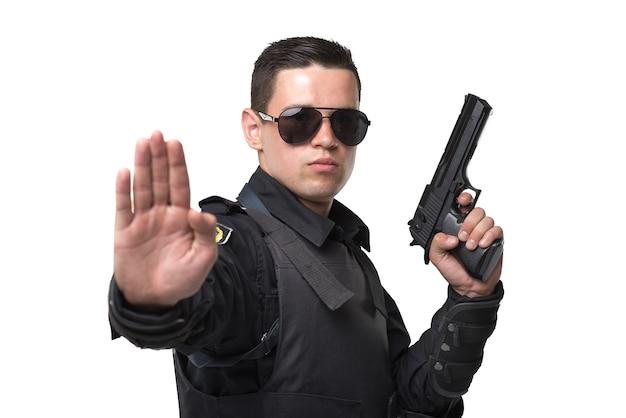 Policial sério usando óculos escuros posa com arma