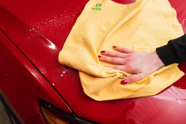 Polimento de carro com pano de microfibra amarelo. proteção da pintura.