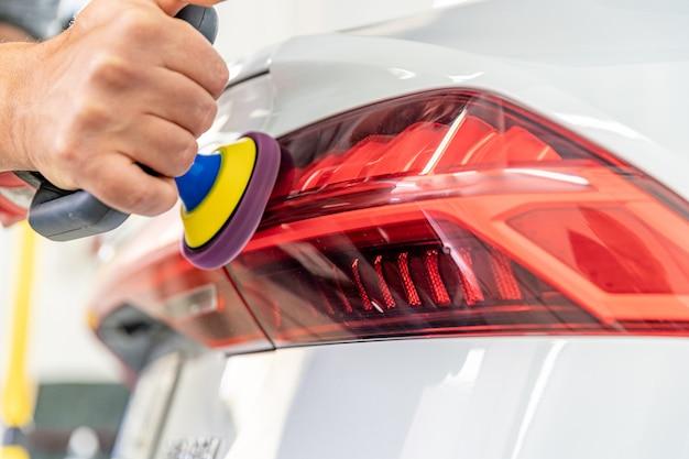 Polimento manual dos faróis de carros de luxo com a aplicação de equipamentos de proteção
