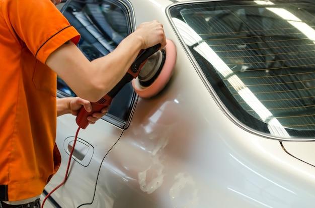 Polimento na superfície do carro. mão e almofada de espuma no movimento borrão