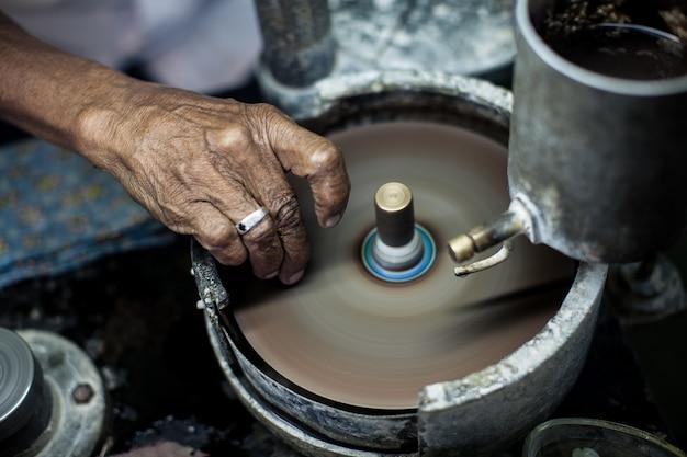 Polimento pedra-da-lua na fábrica para a extração e processamento de pedras preciosas.