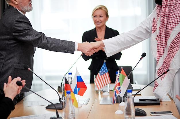 Políticos caucasianos e árabes apertando as mãos após acordo, pessoas reduzidas assinaram documento bilateral