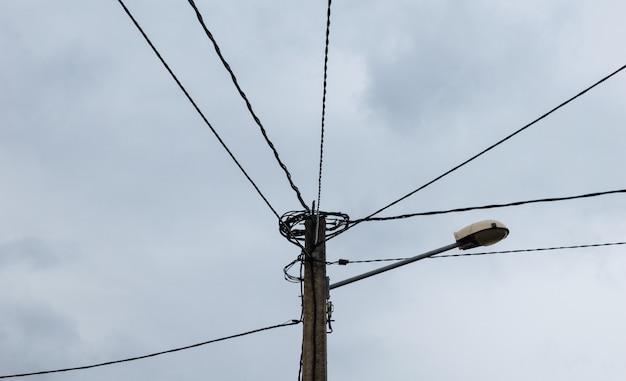 Pólo elétrico com muitos cabos de linhas elétricas e uma lâmpada de rua.