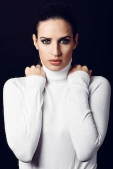 Poloneck branco vestindo da mulher moreno nova. garota atraente, modelo da moda.