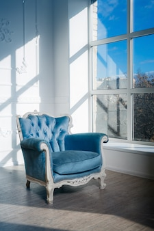 Poltrona azul está na sala perto da janela