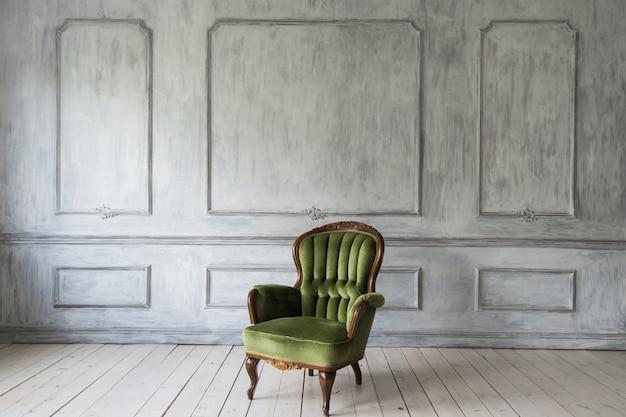 Poltrona clássica contra uma parede e piso brancos. copie o espaço