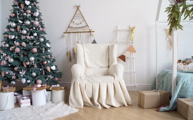 Poltrona coberta clássica ao lado da árvore de natal decorada com uma escada e um apanhador de sonhos pendurado na parede