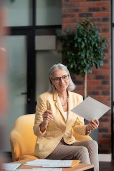 Poltrona confortável. mulher de negócios sorridente com roupas da moda, sentada em uma poltrona amarela confortável, segurando um documento na mão