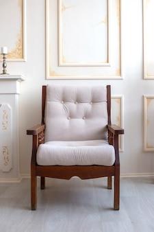 Poltrona de madeira com assento branco macio fica no fundo bege antigo da parede