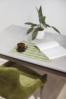 Poltrona e mesa loft de veludo verde para local de trabalho minimalista e moderna com planta em vaso branco