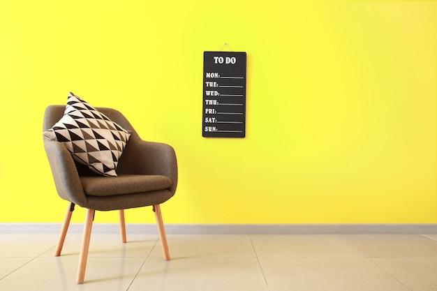 Poltrona elegante perto da parede colorida do quarto
