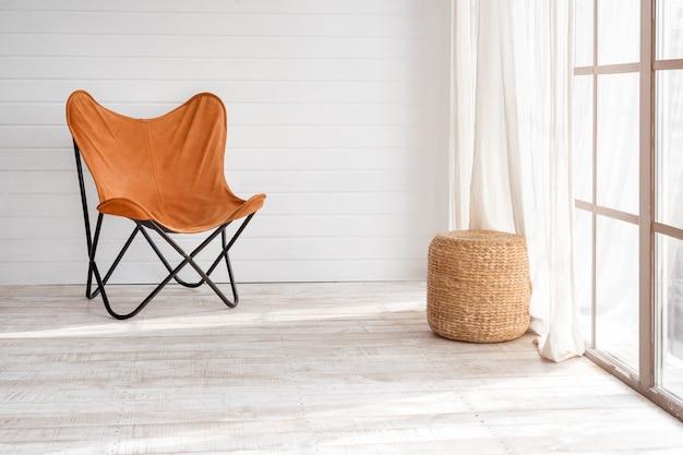 Poltrona moderna no interior moderno apartamento. dia de sol na luminosa sala de estar com janelas panorâmicas.