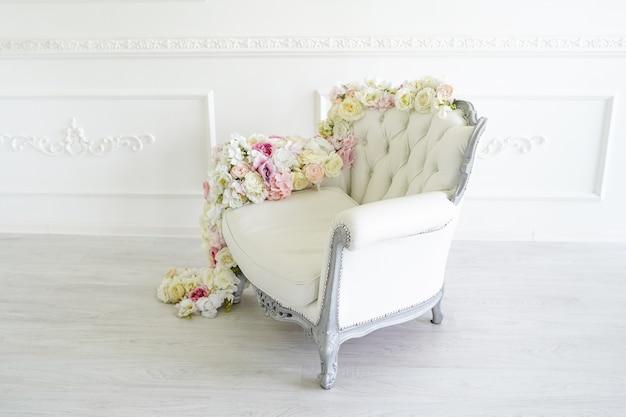 Poltrona no quarto branco. belo interior, decorado com flores.