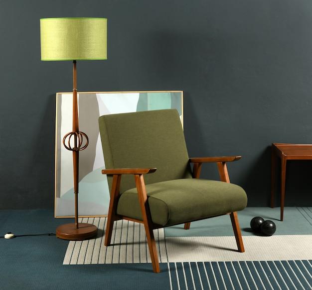 Poltrona retro dos anos 70 colocada no tapete perto da lâmpada e uma imagem abstrata contra a parede cinza