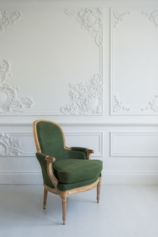 Poltrona verde elegante no interior branco limpo brilhante de luxo