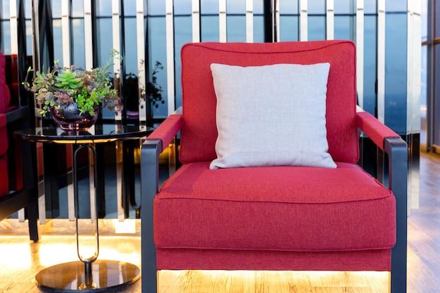 Poltrona vermelha do algodão do close up com o coxim perto da mesa de centro preta na sala de visitas.