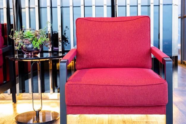 Poltrona vermelha do algodão do close up perto da mesa de centro preta na sala de visitas.