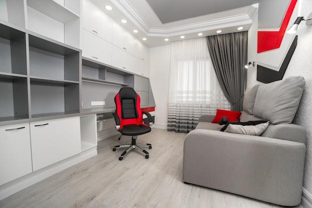 Poltrona vermelha e preta no escritório com móveis brancos