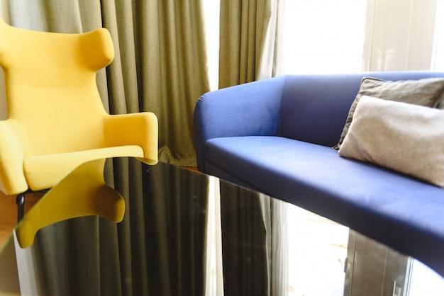 Poltronas e sofá de cores modernas em um salão de um hotel.