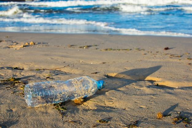 Poluição ambiental: garrafa de plástico na praia
