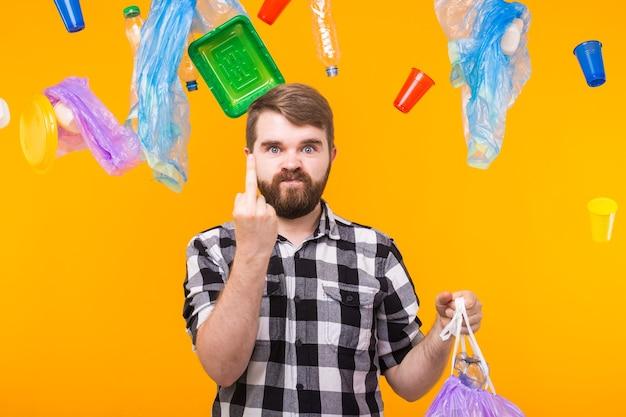 Poluição ambiental, problema de reciclagem de plástico e conceito de eliminação de resíduos - homem bravo segurando um saco de lixo
