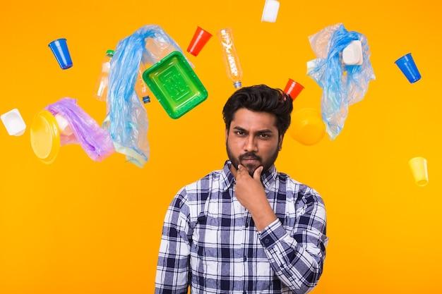 Poluição ambiental, problema de reciclagem de plástico e conceito de eliminação de resíduos - homem indiano preocupado