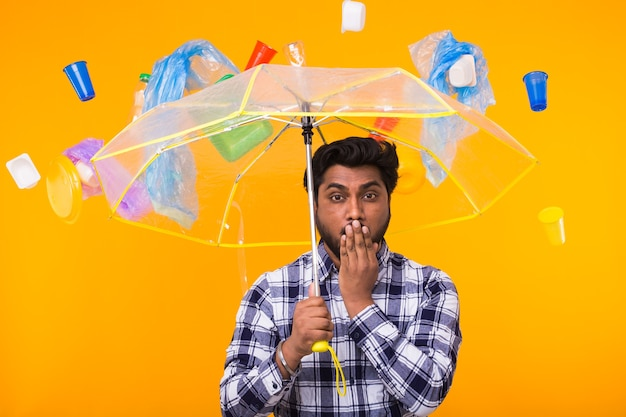 Poluição ambiental, problema de reciclagem de plástico e conceito de eliminação de resíduos - homem indiano surpreso