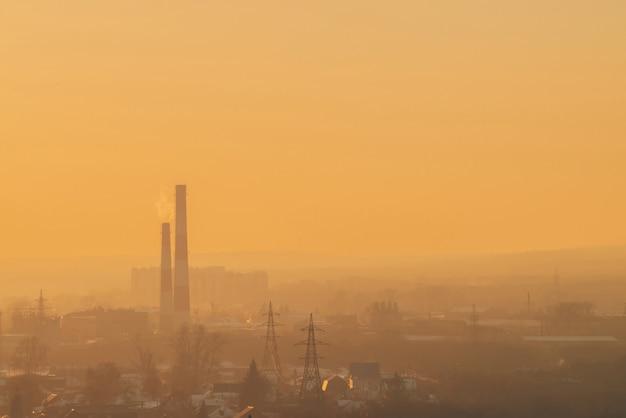 Poluição atmosférica entre as silhuetas dos edifícios no nascer do sol.