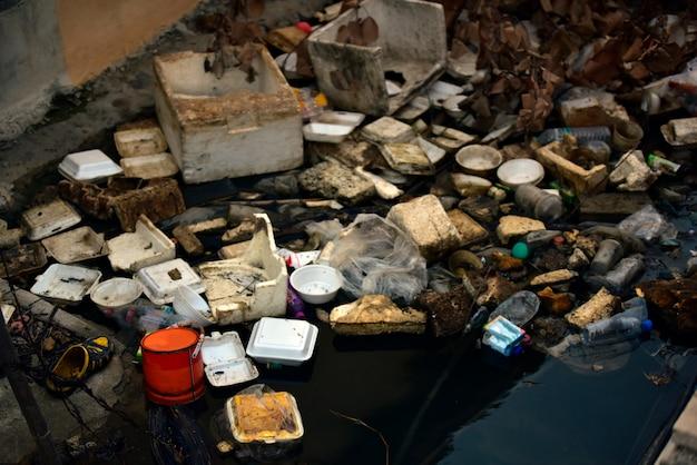 Poluição da praia. garrafas de plástico e outro lixo no rio.