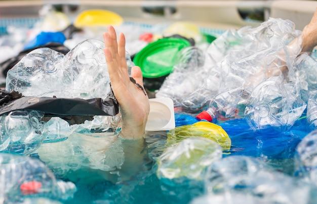 Poluição de plástico e problema ambiental, a mão do homem no mar de plástico