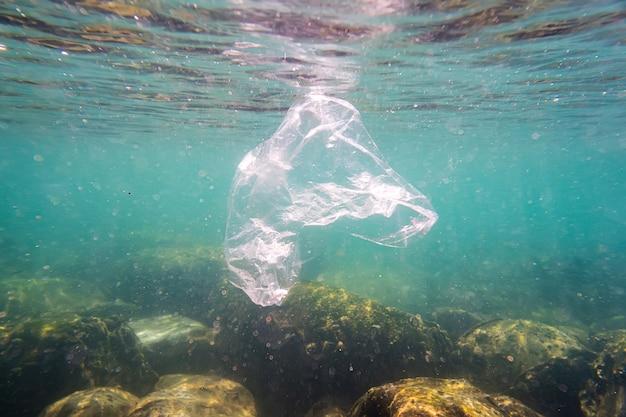 Poluição de plástico um saco de lixo plástico descartado flutua em um recife de coral tropical, apresentando um risco para a vida marinha