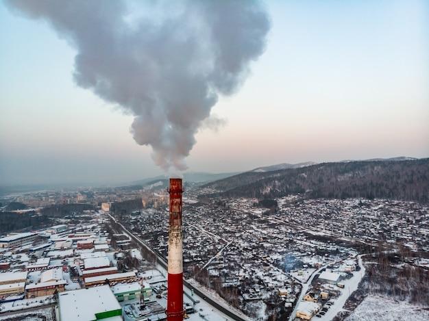 Poluição de uma chaminé da fábrica na superfície do céu puro
