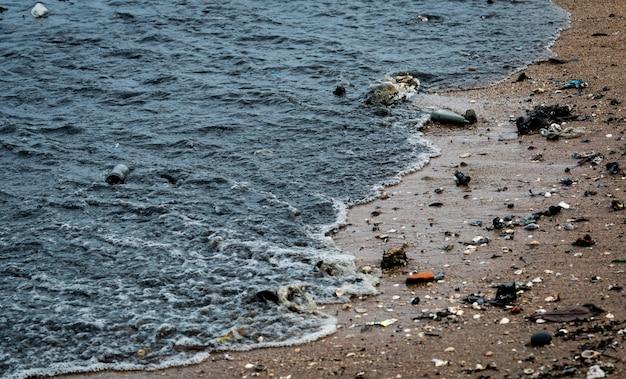 Poluição do ambiente de praia. manchas de óleo na praia. vazamento de óleo para o mar. água suja no oceano. poluição da água. nocivo para os animais no ambiente oceano e mar. água de esgoto.