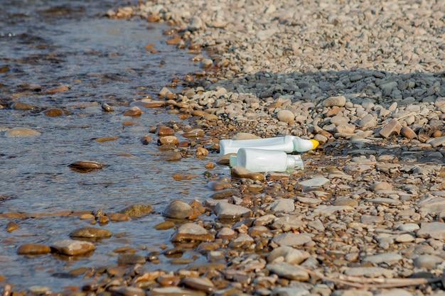 Poluição do rio perto da costa, lixo perto do rio, resíduos de alimentos em plástico, contribuindo para a poluição