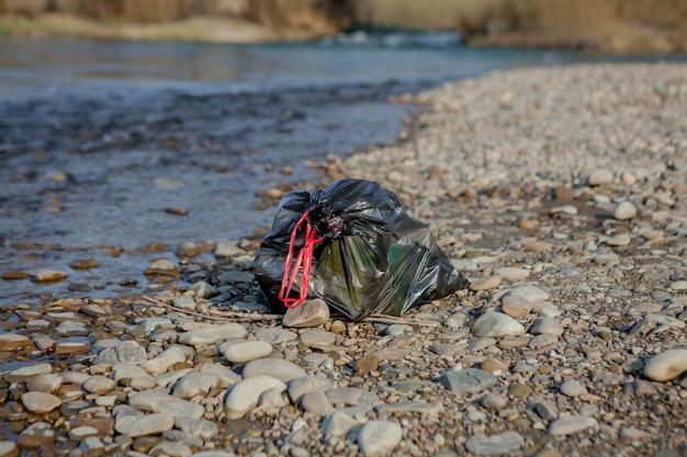 Poluição do rio perto da costa, pacote de lixo perto do rio, resíduos de alimentos plásticos, contribuindo para a poluição