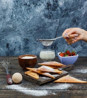 Polvilhando farinha à mão no waffle na placa de madeira