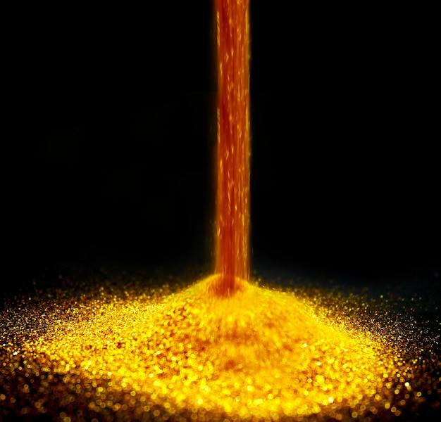 Polvilhe a poeira de ouro em um fundo preto com o espaço da cópia. pó de ouro brilho em backg preto