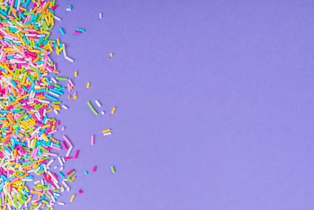 Polvilhe pontos de açúcar, decoração para bolo e padaria, como pano de fundo. isolado em roxo.