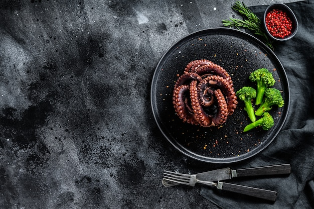 Polvo cozido com brócolis em um prato. superfície preta. vista do topo. copie o espaço