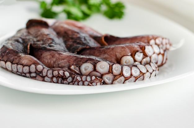 Polvo cru fresco na chapa branca. conceito de frutos do mar mediterrâneo. copie o espaço