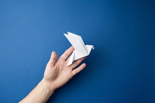 Pombo de origami em mãos humanas em uma parede azul isolada. conceito do dia mundial da paz.