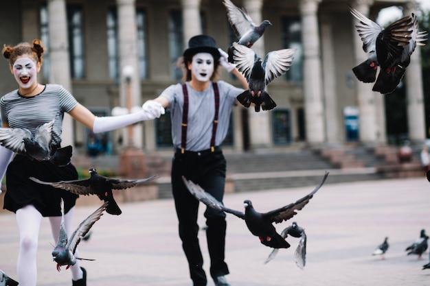 Pombos voando na frente do casal mime correndo